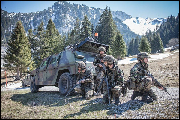 Swiss Forces deploy around their Mowag Eagle reconnaissance vehicle.